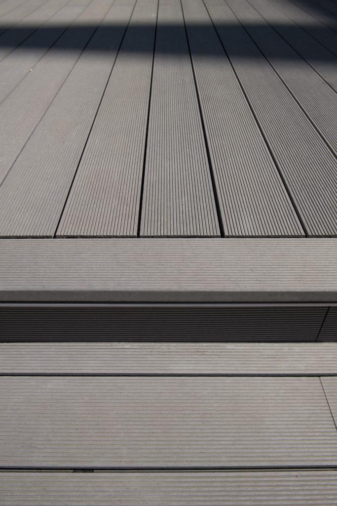 Gros plan sur une terrasse en bois composite LAMEO - lame XTRA coloris béton face striée